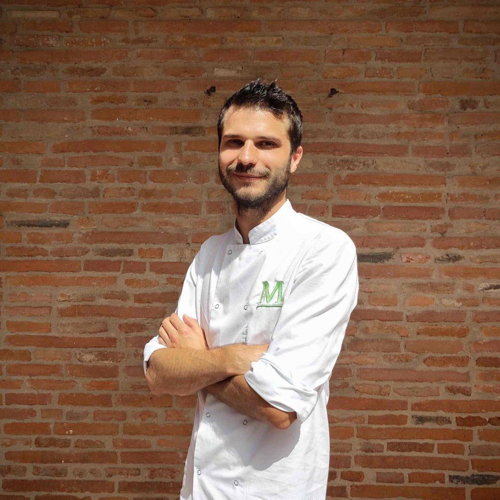 portrait du Chef pâtissier de profil devant un mur en briques