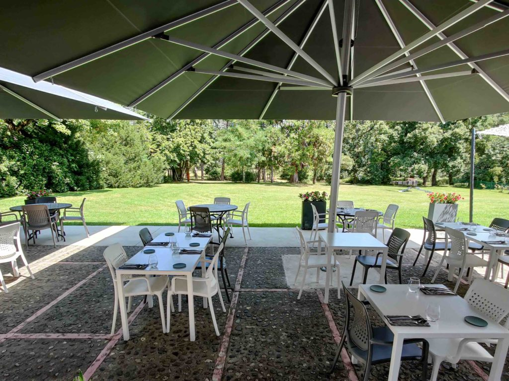 photo de la terrasse avec les parasols déployés. En arrière-plan se trouve le jardin du Domaine